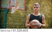 Купить «A man standing on a sports ground and holding a basketball ball», видеоролик № 31529603, снято 20 ноября 2019 г. (c) Константин Шишкин / Фотобанк Лори