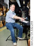 Купить «Musician male is choosing keyboard and playing on it», фото № 31532219, снято 18 сентября 2017 г. (c) Яков Филимонов / Фотобанк Лори