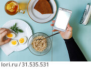 Купить «Healthy breakfast. Young business woman or Young student eats breakfast at the table at home or at a coffee shop or at the desk in the office. top veiw», фото № 31535531, снято 16 декабря 2019 г. (c) easy Fotostock / Фотобанк Лори