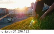 Купить «Young ballerina ties a bow on her pointe sitting on the green hill.», видеоролик № 31596183, снято 27 мая 2020 г. (c) Константин Шишкин / Фотобанк Лори