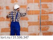 Купить «Workman is plastering the wall at the place», фото № 31596347, снято 6 марта 2019 г. (c) Яков Филимонов / Фотобанк Лори