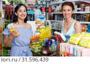 Купить «Lucky woman seller helping to girl customer», фото № 31596439, снято 21 июня 2018 г. (c) Яков Филимонов / Фотобанк Лори