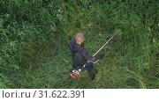 Купить «Рабочий косит траву ручной бензиновой газонокосилкой. Вид сверху», видеоролик № 31622391, снято 17 июля 2019 г. (c) А. А. Пирагис / Фотобанк Лори