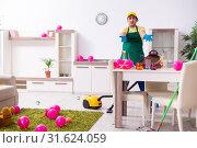 Купить «Young male contractor doing housework after party», фото № 31624059, снято 14 марта 2019 г. (c) Elnur / Фотобанк Лори