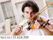 Купить «Young musician man practicing playing violin at home», фото № 31624399, снято 17 января 2019 г. (c) Elnur / Фотобанк Лори