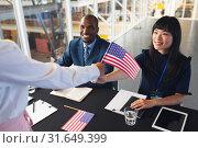 Купить «Business people holding an American flag at conference registration table», фото № 31649399, снято 16 марта 2019 г. (c) Wavebreak Media / Фотобанк Лори