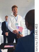 Купить «Businessman holding an American flag at conference registration table», фото № 31649403, снято 16 марта 2019 г. (c) Wavebreak Media / Фотобанк Лори