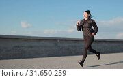 Sporty caucasian lady runs outdoors near the sea early morning slow motion. Стоковое видео, видеограф Denis Mishchenko / Фотобанк Лори