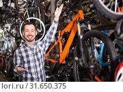 Купить «friendly man in sports shop treats bicycles and points up on interesting details», фото № 31650375, снято 19 июля 2019 г. (c) Яков Филимонов / Фотобанк Лори