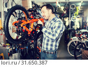 Купить «attentive male mounts bicycle parts for assembly bike in shop», фото № 31650387, снято 23 июля 2019 г. (c) Яков Филимонов / Фотобанк Лори