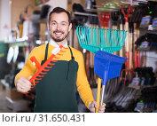 Купить «Cheerful male seller demonstrating assortment», фото № 31650431, снято 2 марта 2017 г. (c) Яков Филимонов / Фотобанк Лори