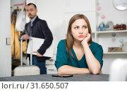 Купить «Offended woman at table on background with man leaving her», фото № 31650507, снято 15 января 2019 г. (c) Яков Филимонов / Фотобанк Лори