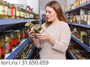 Купить «Serious female looking pickle goods in grocery section», фото № 31650659, снято 11 апреля 2018 г. (c) Яков Филимонов / Фотобанк Лори