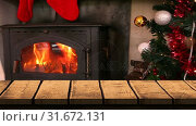 Купить «Wooden foreground with Christmas background of tree and fire», видеоролик № 31672131, снято 24 сентября 2018 г. (c) Wavebreak Media / Фотобанк Лори