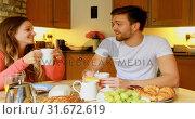 Купить «Couple having coffee on dining table in kitchen 4k», видеоролик № 31672619, снято 11 июля 2018 г. (c) Wavebreak Media / Фотобанк Лори