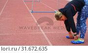 Купить «Female athlete exercising on a running track 4k», видеоролик № 31672635, снято 17 апреля 2018 г. (c) Wavebreak Media / Фотобанк Лори