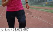 Купить «Front view of Caucasian female athlete exercising on running track at sports venue 4k», видеоролик № 31672687, снято 17 апреля 2018 г. (c) Wavebreak Media / Фотобанк Лори