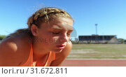 Купить «Front view of Caucasian female athlete taking a break on a sports track 4k», видеоролик № 31672811, снято 17 апреля 2018 г. (c) Wavebreak Media / Фотобанк Лори