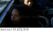 Купить «Girl looking through window while travelling in bus 4k», видеоролик № 31672919, снято 10 июня 2018 г. (c) Wavebreak Media / Фотобанк Лори