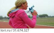 Купить «Side view of Caucasian female athlete drinking water on race track 4k», видеоролик № 31674327, снято 17 апреля 2018 г. (c) Wavebreak Media / Фотобанк Лори