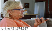 Senior woman talking on mobile phone in living room 4k. Стоковое видео, агентство Wavebreak Media / Фотобанк Лори