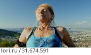 Senior woman listening music on headphones at countryside 4k. Стоковое видео, агентство Wavebreak Media / Фотобанк Лори