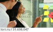 Купить «Executives discussing over sticky note on glass wall 4k», видеоролик № 31698047, снято 1 сентября 2018 г. (c) Wavebreak Media / Фотобанк Лори