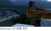 Купить «Fisherman fishing with his dog in the river 4k», видеоролик № 31698107, снято 30 июля 2018 г. (c) Wavebreak Media / Фотобанк Лори