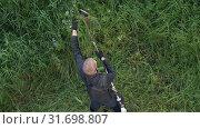 Купить «Рабочий косит траву ручной бензиновой газонокосилкой. Вид сверху, zoom in», видеоролик № 31698807, снято 17 июля 2019 г. (c) А. А. Пирагис / Фотобанк Лори