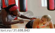 Купить «Trainer training female boxer in fitness studio 4k», видеоролик № 31698843, снято 6 сентября 2018 г. (c) Wavebreak Media / Фотобанк Лори