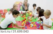 Купить «Group of schoolkids playing with toy bricks in circle with their cheerful female teacher», видеоролик № 31699043, снято 18 декабря 2018 г. (c) Яков Филимонов / Фотобанк Лори