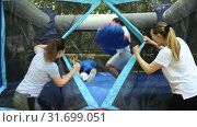 Купить «Gambling friends boxing giant gloves on an inflatable trampoline in an amusement park», видеоролик № 31699051, снято 29 мая 2019 г. (c) Яков Филимонов / Фотобанк Лори