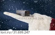 Купить «Santa clause holding a present in his hand combined with falling snow», видеоролик № 31699247, снято 2 ноября 2018 г. (c) Wavebreak Media / Фотобанк Лори