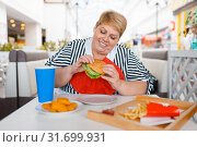 Купить «Fat woman eating fastfood in mall food court», фото № 31699931, снято 24 мая 2019 г. (c) Tryapitsyn Sergiy / Фотобанк Лори