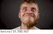 Handsome bearded hipster male looks like crazy a in the black studio. Стоковое видео, видеограф Dzmitry Astapkovich / Фотобанк Лори