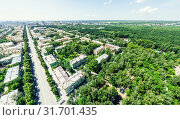 Купить «Aerial city view with crossroads and roads, houses, buildings, parks and parking lots. Sunny summer panoramic image», фото № 31701435, снято 21 января 2020 г. (c) Александр Маркин / Фотобанк Лори