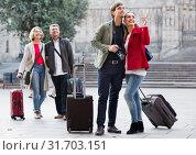 Купить «Two couples with baggage sightseeing and smiling», фото № 31703151, снято 24 августа 2019 г. (c) Яков Филимонов / Фотобанк Лори