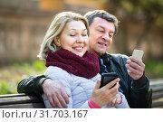 Купить «Mature couple with smartphones outdoors», фото № 31703167, снято 23 августа 2019 г. (c) Яков Филимонов / Фотобанк Лори