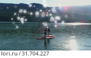 Купить «Couple doing paddle board surrounded by white bubbles effect», видеоролик № 31704227, снято 5 марта 2019 г. (c) Wavebreak Media / Фотобанк Лори