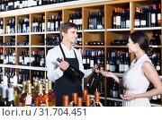 Купить «portrait of male seller showing bottle of wine to female customer in wine shop», фото № 31704451, снято 6 июня 2020 г. (c) Яков Филимонов / Фотобанк Лори