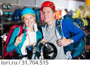 Купить «Laughing couple is choosing travel gear in shop», фото № 31704515, снято 25 октября 2017 г. (c) Яков Филимонов / Фотобанк Лори