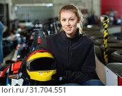 Купить «Young woman with helmet sitting in car for karting in sport club», фото № 31704551, снято 18 марта 2019 г. (c) Яков Филимонов / Фотобанк Лори
