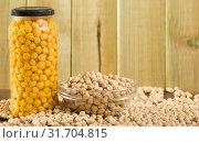 Купить «Glass jar with boiled chickpeas and bowl of raw chickpea grains on wooden surface», фото № 31704815, снято 7 декабря 2019 г. (c) Яков Филимонов / Фотобанк Лори