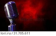 Купить «Microphone on a red and black background», видеоролик № 31705611, снято 25 апреля 2019 г. (c) Wavebreak Media / Фотобанк Лори