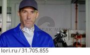 Купить «Male mechanic wearing uniform in motorbike repair garage 4k», видеоролик № 31705855, снято 10 февраля 2019 г. (c) Wavebreak Media / Фотобанк Лори