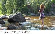 Купить «A girl stands barefoot on a stone in the water», видеоролик № 31762427, снято 19 августа 2018 г. (c) Aleksandr Sulimov / Фотобанк Лори