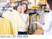Купить «Asistant demonstration fashion yellow pullover to woman in boutique», фото № 31765459, снято 15 марта 2018 г. (c) Яков Филимонов / Фотобанк Лори