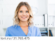 Купить «Doctor girl stands near a table in the office», фото № 31765475, снято 17 октября 2017 г. (c) Яков Филимонов / Фотобанк Лори