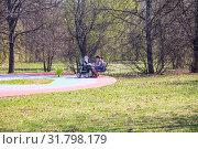 Купить «Женщина с коляской отдыхает в весеннем парке, Москва», фото № 31798179, снято 25 апреля 2019 г. (c) Наталия Шевченко / Фотобанк Лори