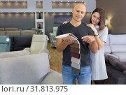 Купить «Husband and wife in process of choosing upholstery fabric», фото № 31813975, снято 29 октября 2018 г. (c) Яков Филимонов / Фотобанк Лори